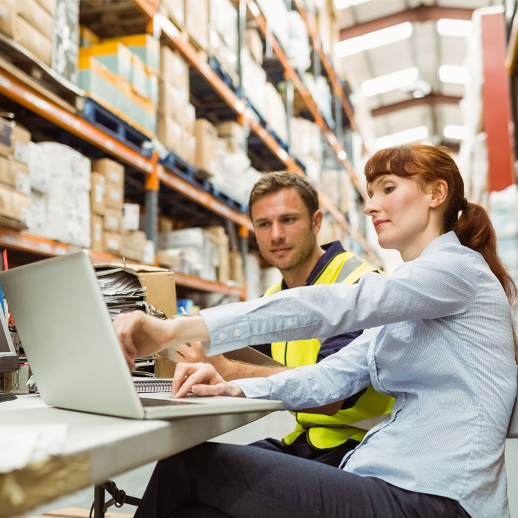 Woman in warehouse showing colleague laptop